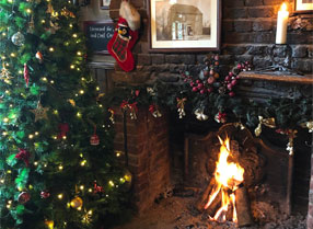 Christmas tree and open fire alight in the hearth.