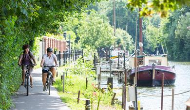 Two cyclists on path next to the River Medway