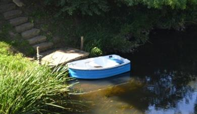 Row boat on the river next to the gallery