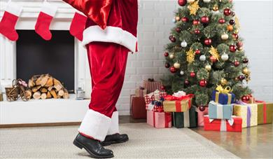 Father Christmas legs, fireplace, Christmas tree and gifts.